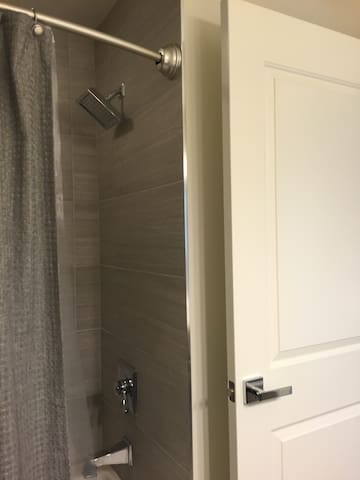 New tiled bath with oversized shower head
