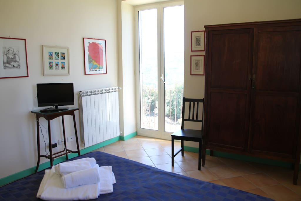 The Bedroom: the comfortable double bed with soft bed-linen and towels & the balcony
