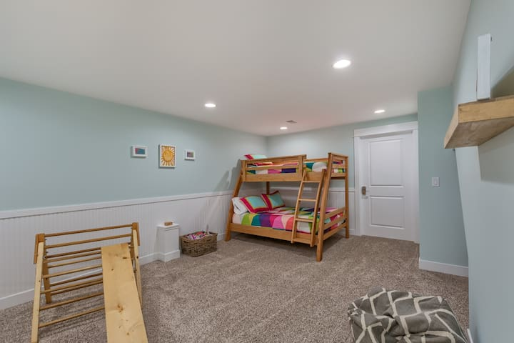 lower level kids room with twin over full bunk, toys, and books