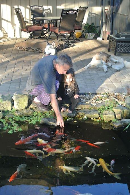 Juan feeding the koi with granddaughter's help