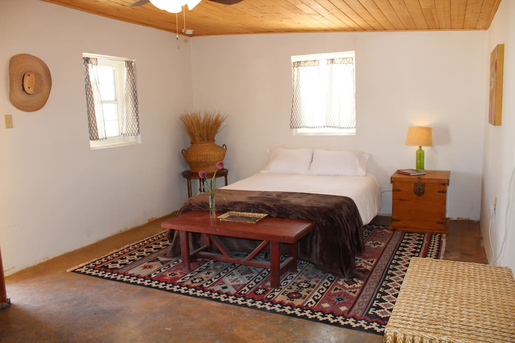 Queen bed in the entry room with an AC unit, overhead fan and front  door.