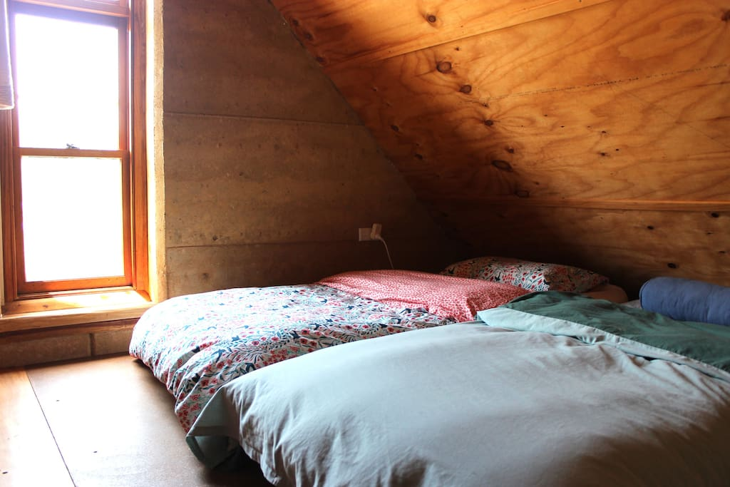 Guest Space:  Loft room with two single beds one lamp and ample clothes hanging rails.