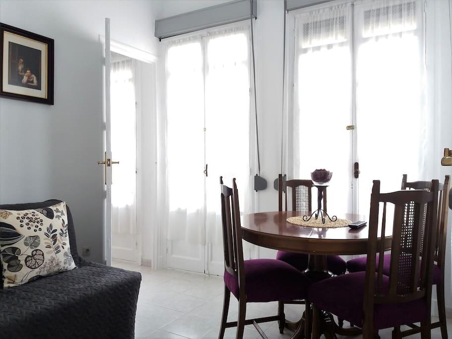 Salón con mesa comedor y sofá-cama.