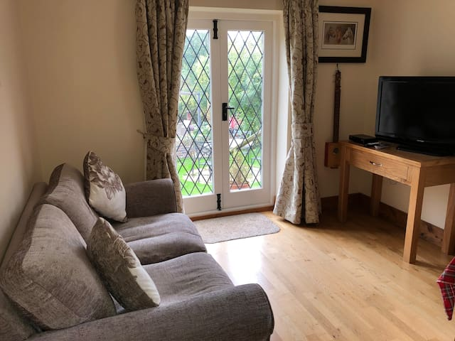 Sitting room looking onto the garden with sofa bed, table and TV.