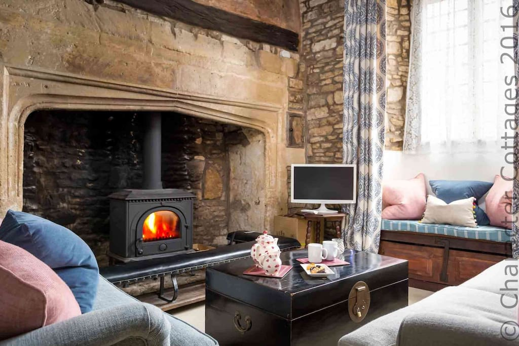 The historic fireplace contains a roaring log burner