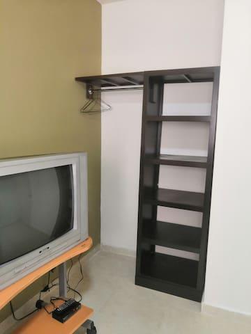 Habitación con 2 camas individuales, closed y TV abierta.