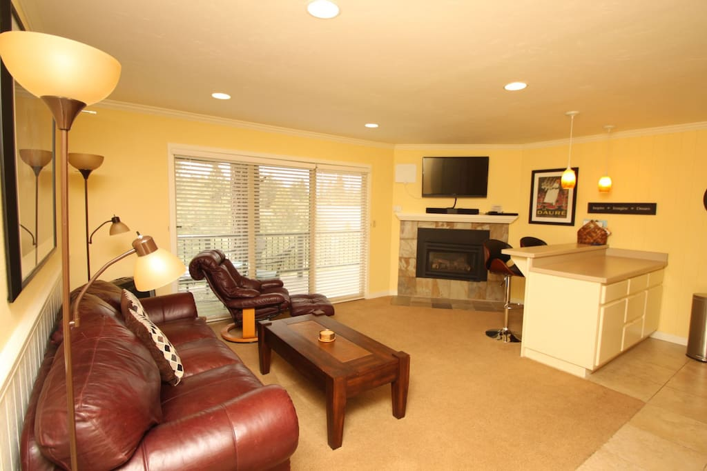 Living room with soft leather sofa, queen sofa sleeper, fireplace and large flat screen LCD