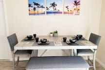 Luxurious dining room with place settings and table set. All the kitchen essentials you need for a great dinner party. Our table also pulls out to fit up to 8 people. Extra cups and plates are located inside the kitchen cupboards