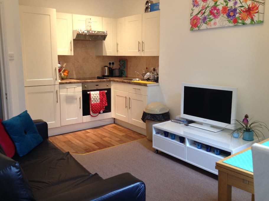 living area with flat tv sofa and open plan kitchen
