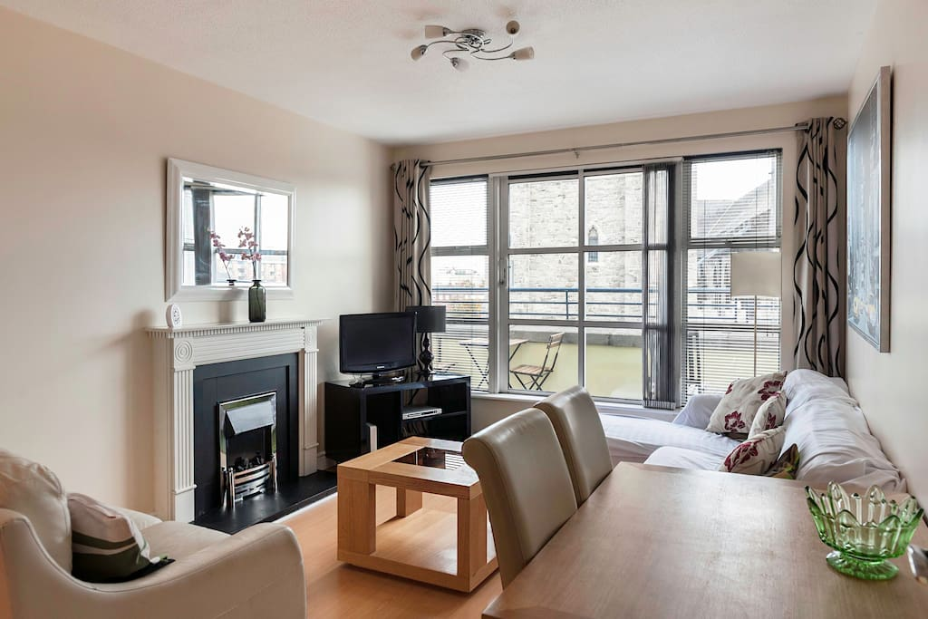 Living/Dining area with access to private balcony. Tv and Hi Speed Wifi located in the corner
