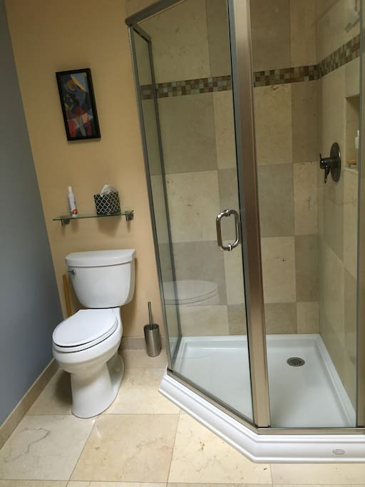 Private bathroom with stone tile in shower and on floor
