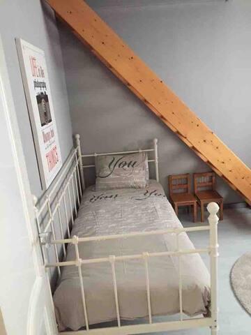 Kleines Schlafzimmer mit ein einzelbett. Treppe zum Estrich.
