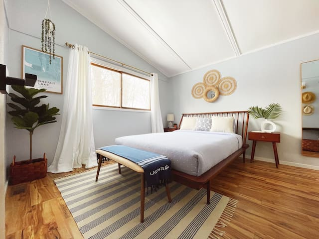 BR 1: Beachy Mid-Century themed-room w/ a queen size bed, spacious barn door closet with luggage rack, iron and ironing board, full-size mirror, laptop table, wall fan, Google Nest speaker.