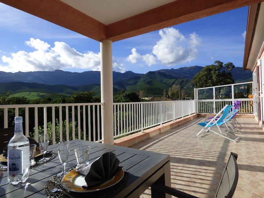 La terrasse, avec coin repas à l'ombre et les transats : tout pour profiter agréablement de ce magnifique paysage