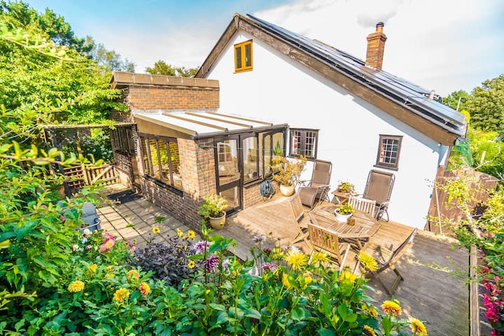The back garden of Badgers Den Cottage has sun loungers, dining table and BBQ area.