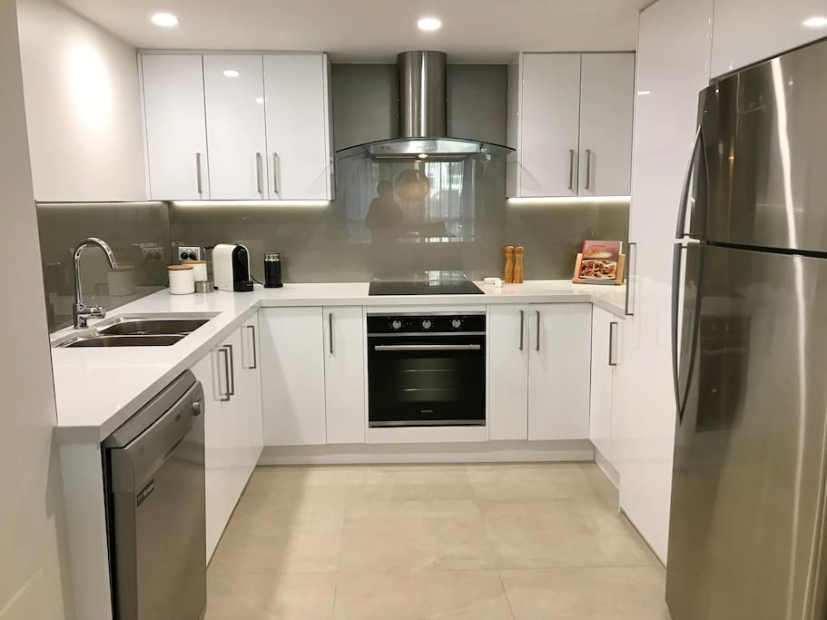 A large kitchen including a coffee pod machine, induction cooktop, dishwasher, stone bench tops, a family size fridge and much more - everything you need in a kitchen to make your stay comfortable.
