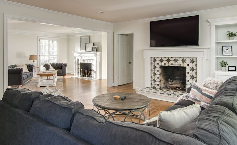 Two large living rooms for gathering with large tv and wood fireplace.