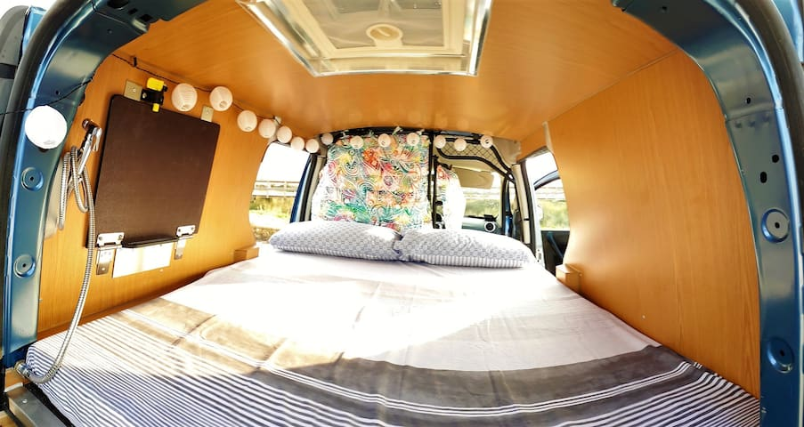 Your bed inside the van. With a comfortable mattress, cosy warm-white LED lights and a little window in the roof. Bedlinen, pillows and towels included.:).
