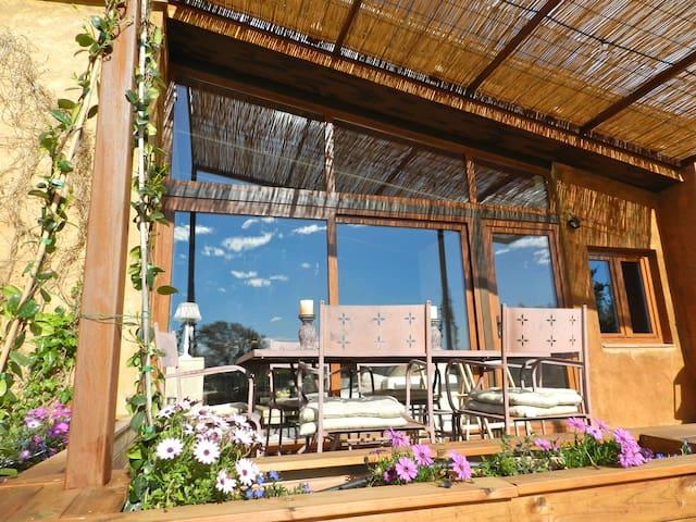 masía con porche de 18 metros, de madera rodeado de jardineras.