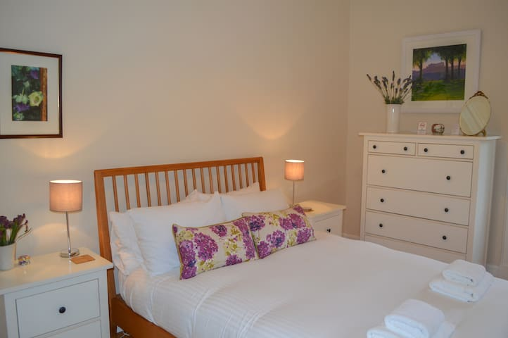 Second bedroom with double Ercol bed and view of communal garden - March 2019