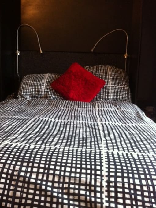 The comfortable double bed hinges up against the wall in the daytime together with the bedding.