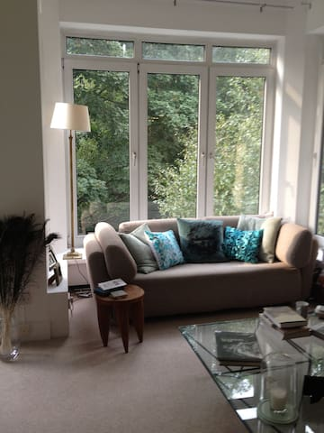 Spacious, light living room. Living room has 6 large floor to ceiling windows, overlooking a communal garden and Hampstead Heath