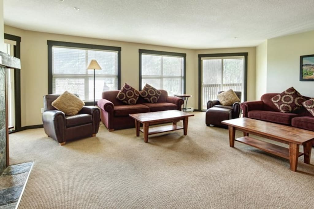 The cozy living room features large windows and a fireplace