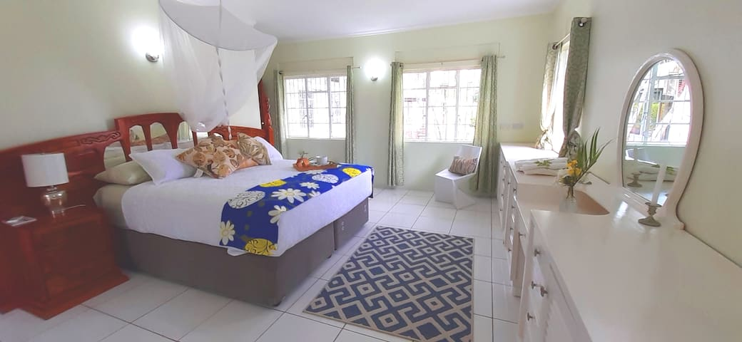bedroom 1 with seaview,  super king size bed, reading lamp, 2 chairs, double wardrobe, extended dresser with storage, dressing mirror, mosquito net, air conditioning unit, with side access to pool