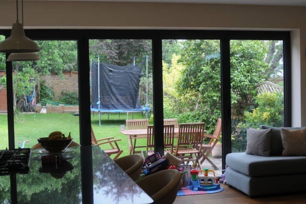 Bi-fold windows open up completely onto the garden which has a hammock, bikes and trampoline
