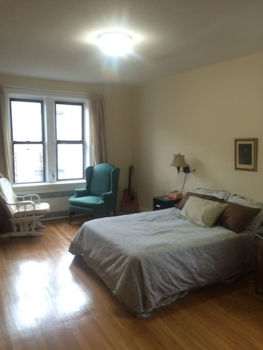 Ample bedroom with comfy chairs by the window and a computer desk (not shown).