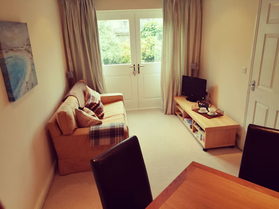 Sitting room with comfortable sofa, TV, CD/radio player, dining table and chairs. French doors to private garden.