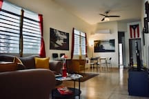 Living room with AC, WIFI, TV, Cable TV, games, stools, one pair of sofas, dinning table with 6 chair, regular and beach towels, armchair and fans.