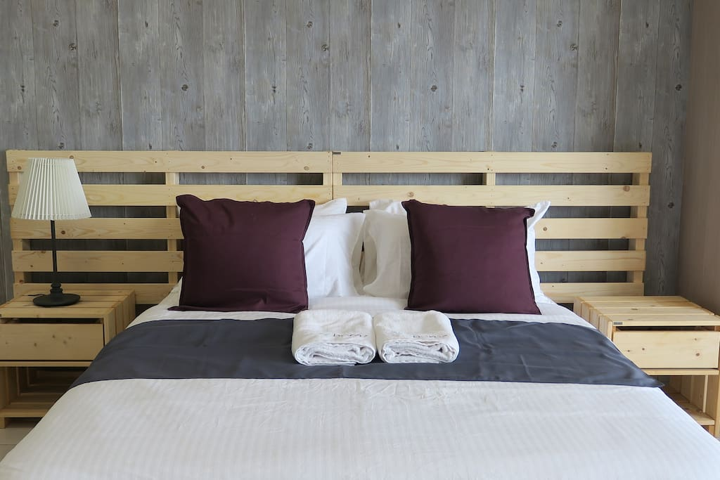 Comfy queen size bed with bed sheets and linen.