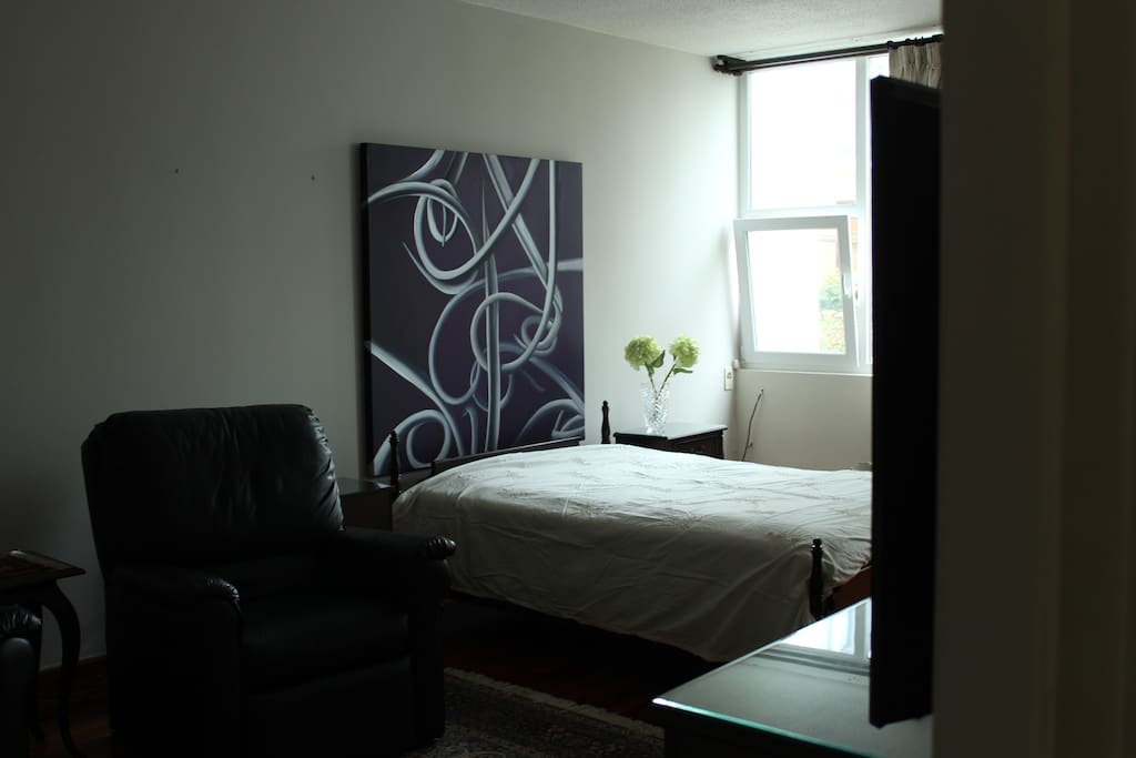 Full-size bed, soundproof windows, and painting by Peruvian artist Anitza Bedoya