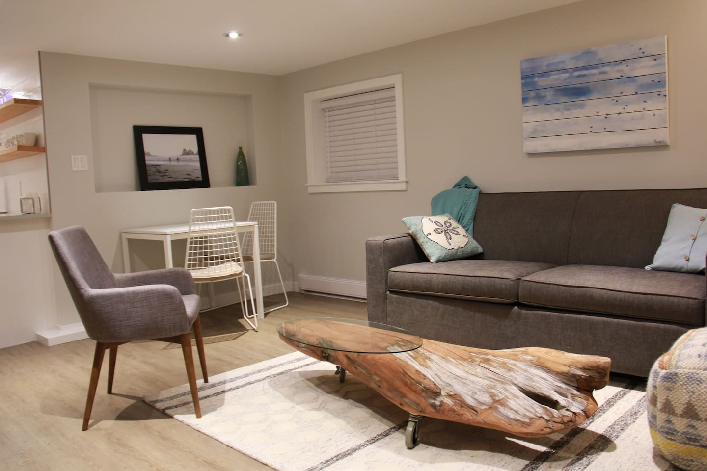 Open concept living and dining space with signature driftwood coffee table.
