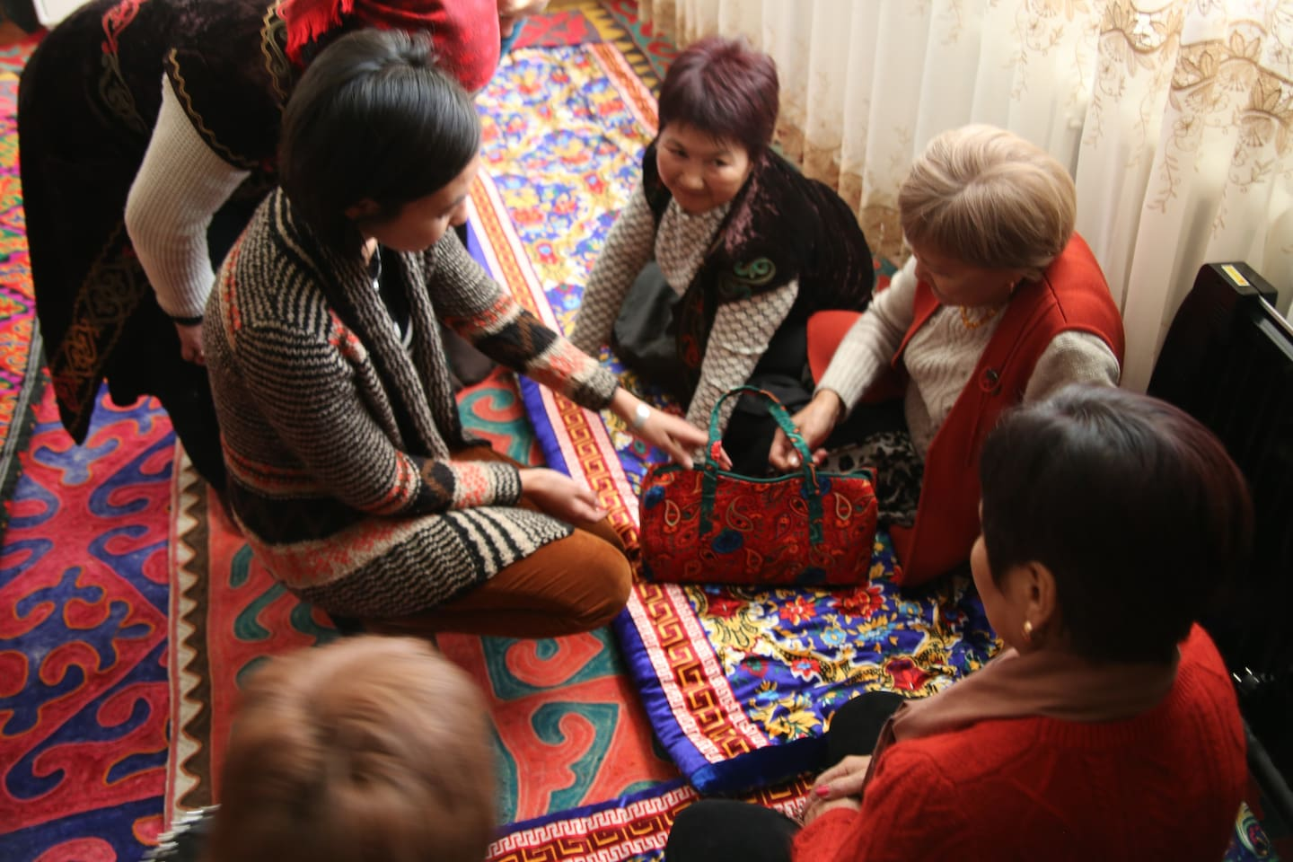 Entire house is decorated with Kyrgyz traditional carpets, wall hangings, and seating cushions.