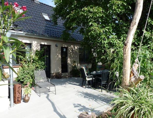 Eingang zur Ferienwohnung und Terrasse mit Sitz-, Liege- und Grillmöglichkeiten