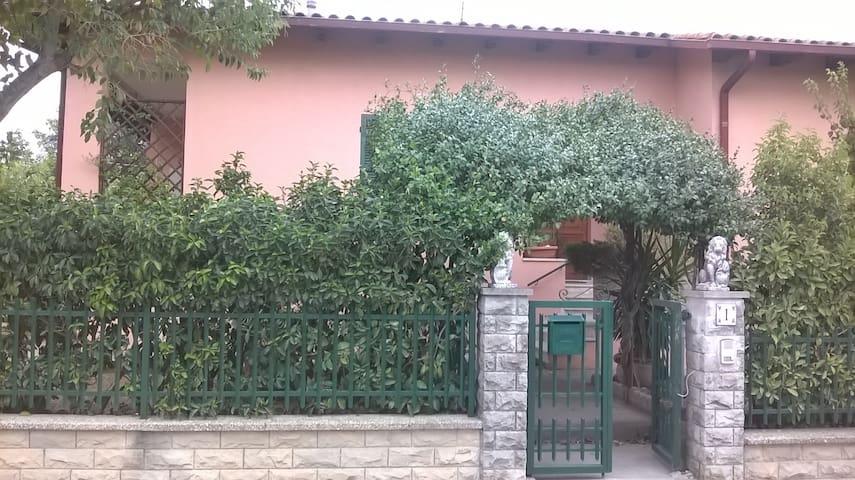 Villetta rosa con giardino e parcheggio privato.