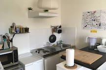 Espace cuisine avec un four, des plaques électriques, un réfrigérateur ainsi qu'une machine à laver.