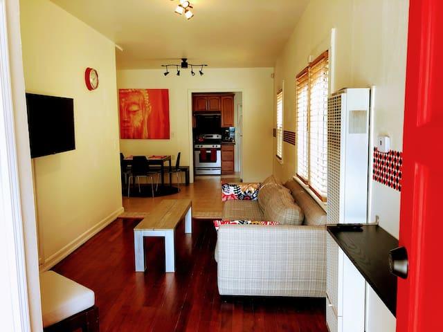 Living room, wall-mounted TV, comfy sofa, gas wall furnace.