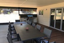 Large outside table seating 12 people in the decked entertaining area, with down lights and BBQ