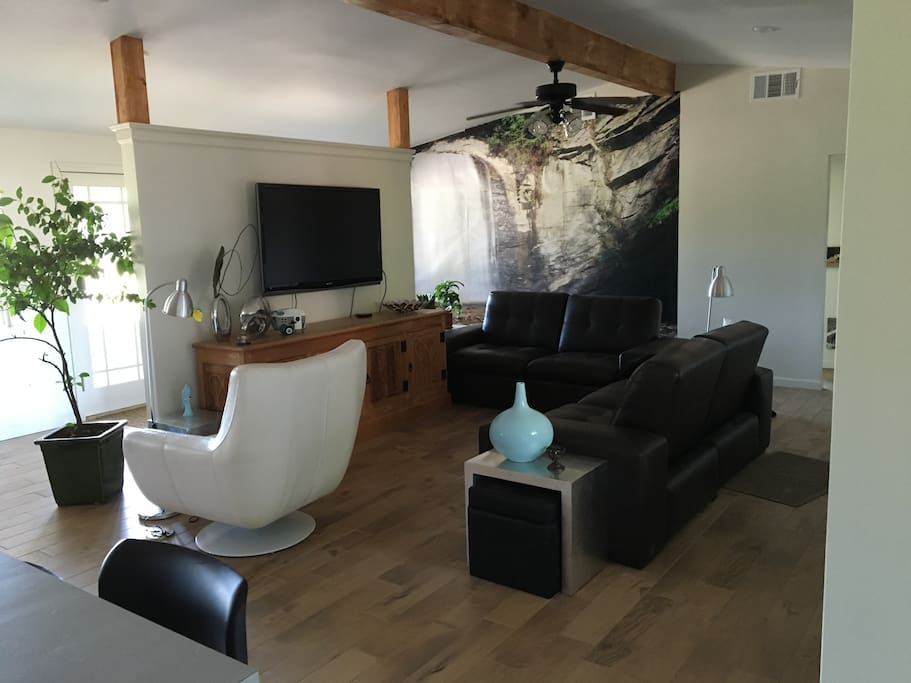 "Open living room with reclining sofas and a 55"" TV"