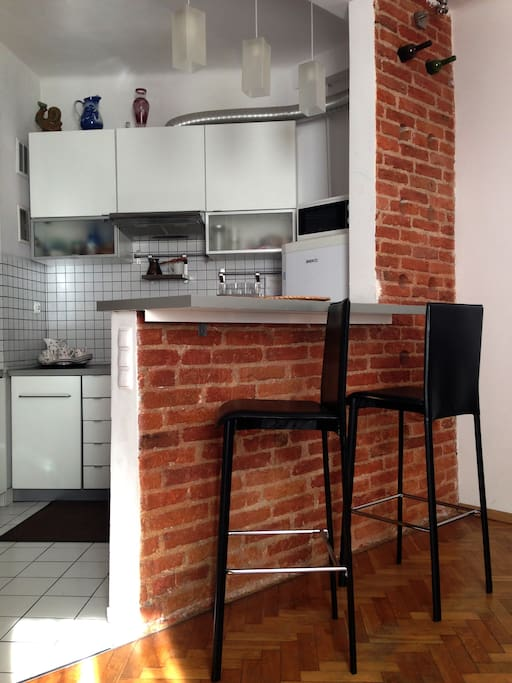 Kitchen with refrigerator, microwave, gas stove, build in oven, dishes