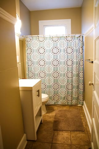 Bathroom off of hallway that is complete with bathtub/shower combo.