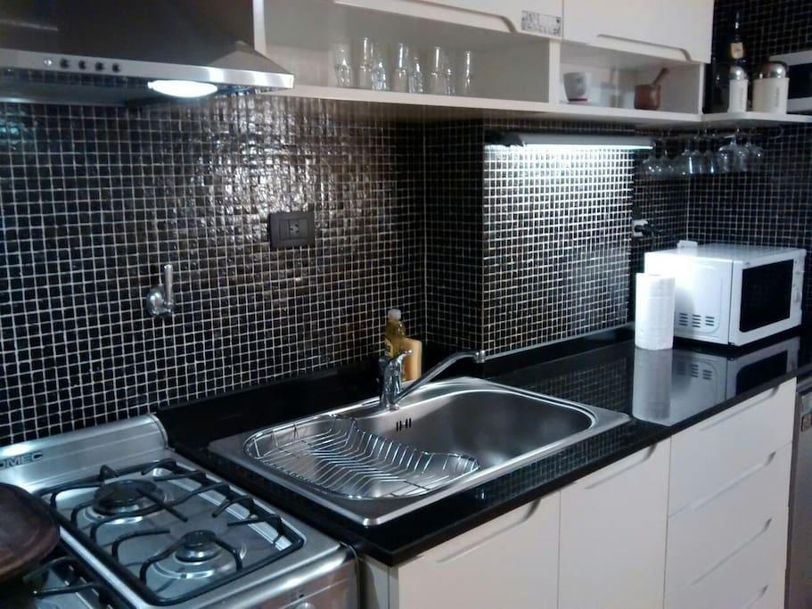 Cocina completa con microondas y equipada con todo lo necesario para una buena estancia.