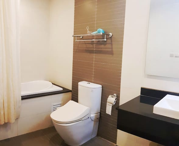 Bathroom with bathtub and modern toilet. It's clean and comfortable. We provide toilet paper, towels, shampoo, bath gel...