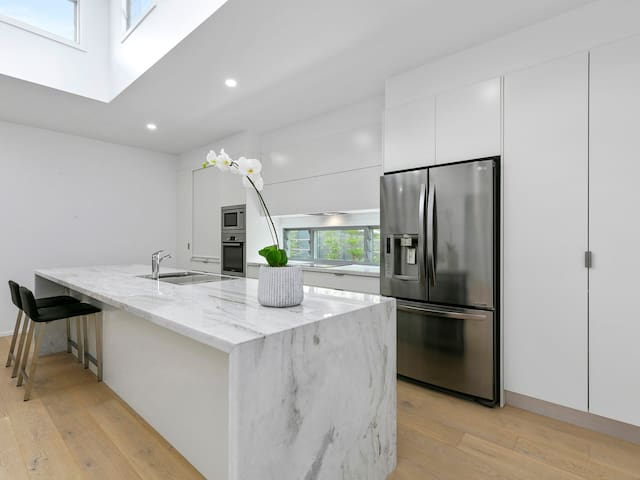 Stone bench tops and modern appliances in a well designed kitchen area