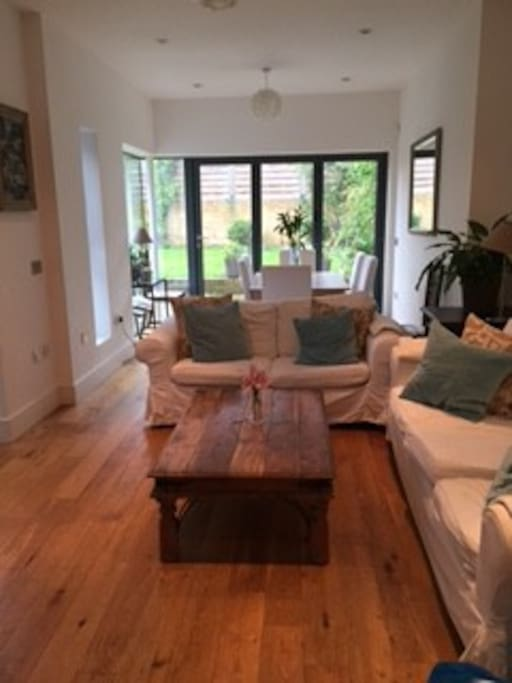 Living/Dining room. Folding doors open to the garden with BBQ outdoor dining.