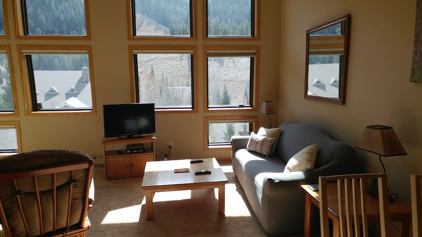 Open Living room with wall of windows and view of the slopes!