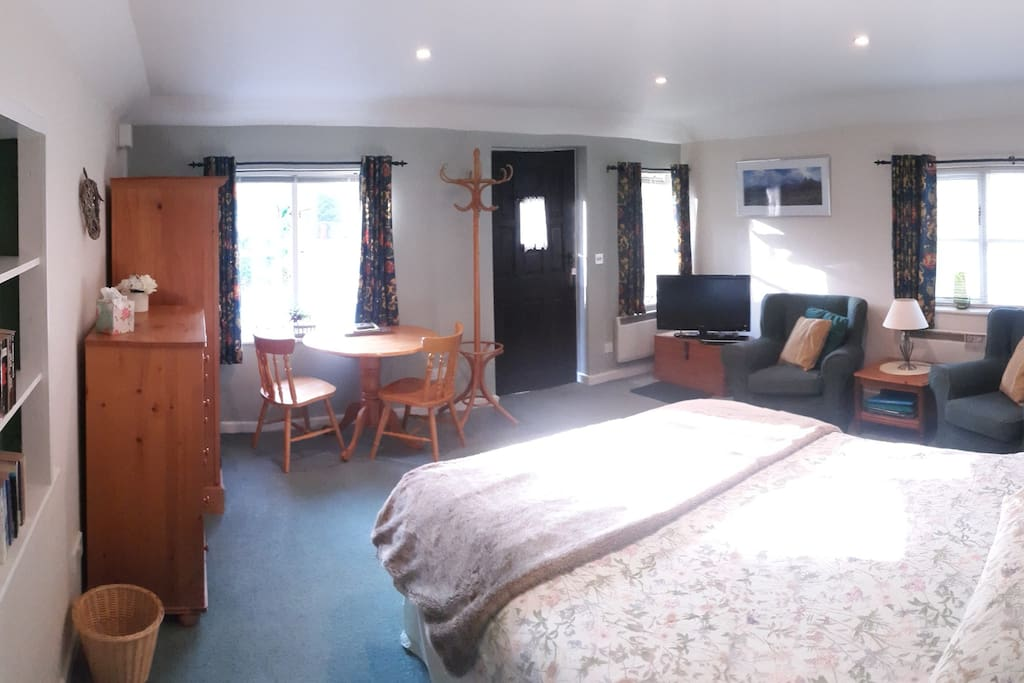 Panoramic view of main room with bed, armchairs and small dining table